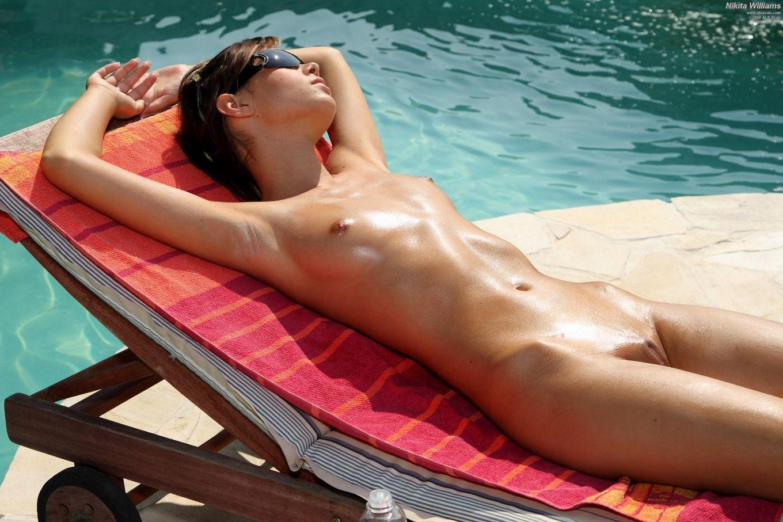 Обнаженная лесбиянка Nikita лежит на солнышке у бассейна и наслаждается глубоким фистингом