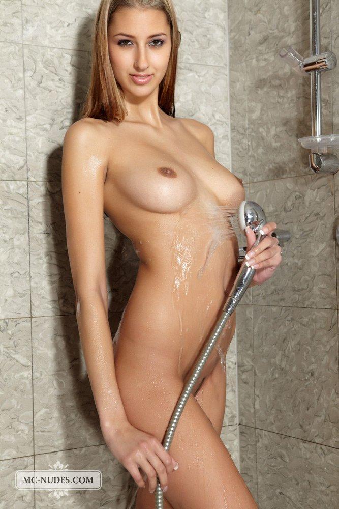 Модель со свелыми волосами Kitty Jane выглядит возбужденно во время того как льет воду на свое голое тело