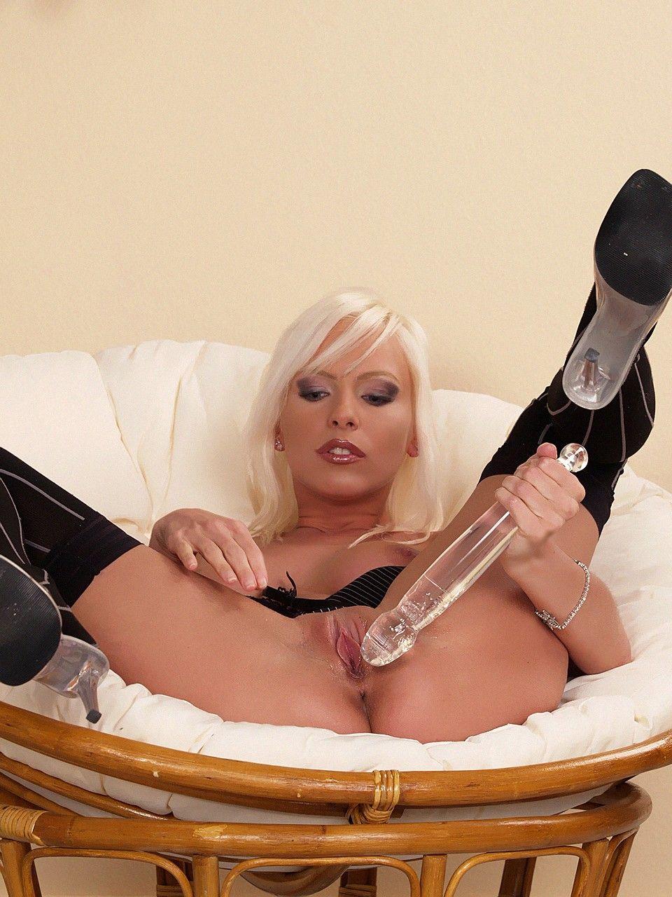 Шикарная блондинка Alexis сидит на комфортабельном стуле и дразнит свою сочную розовую писю стеклянным вибратором