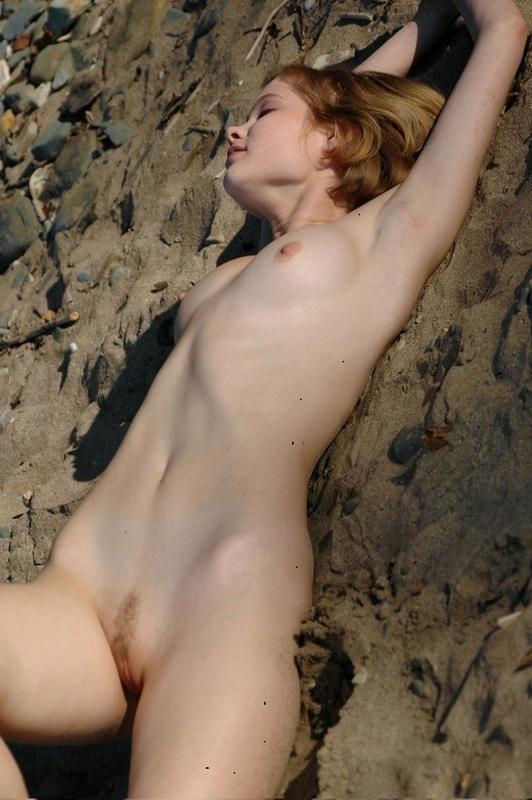Хрупкая баба лежит под солнцем без трусов на фоне озера