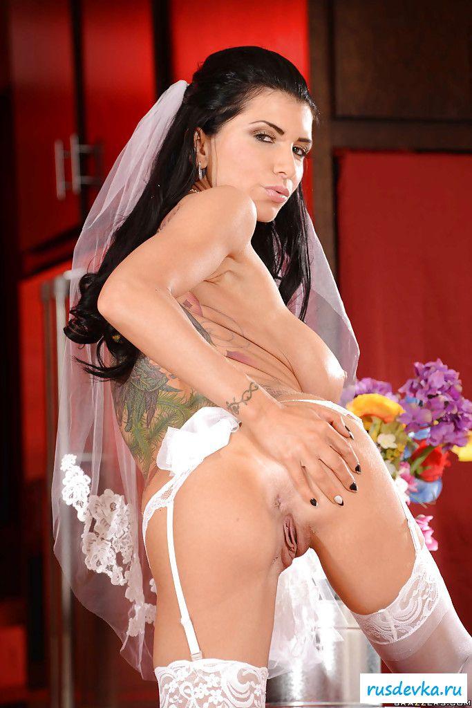 Красавица в венчальном платье снимает лифчик у свадебного стола