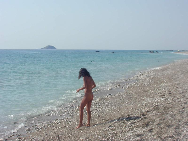 Подтянутая шатенка гуляет на нудистском пляже