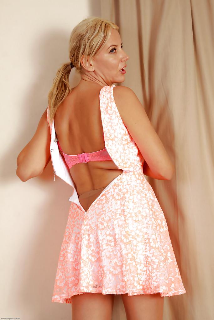 Загорелая светловолосая девушка обнажает большой бюст и розовую вагину