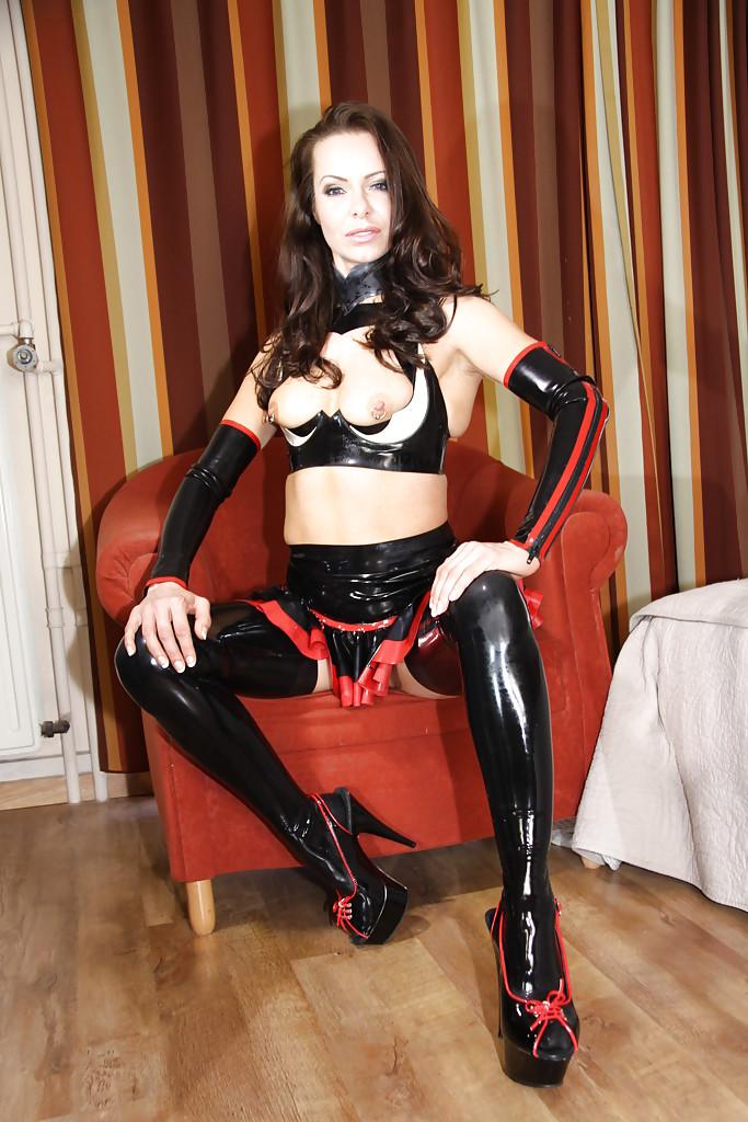 Матерая барышня в латексном наряде блистает тело на красном кресле