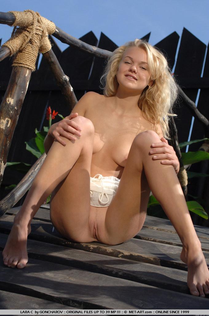 Блондинка с побритой пиздой и возбуждающей красивой попкой Lara C растопыривает свои длинные ножки в лесу