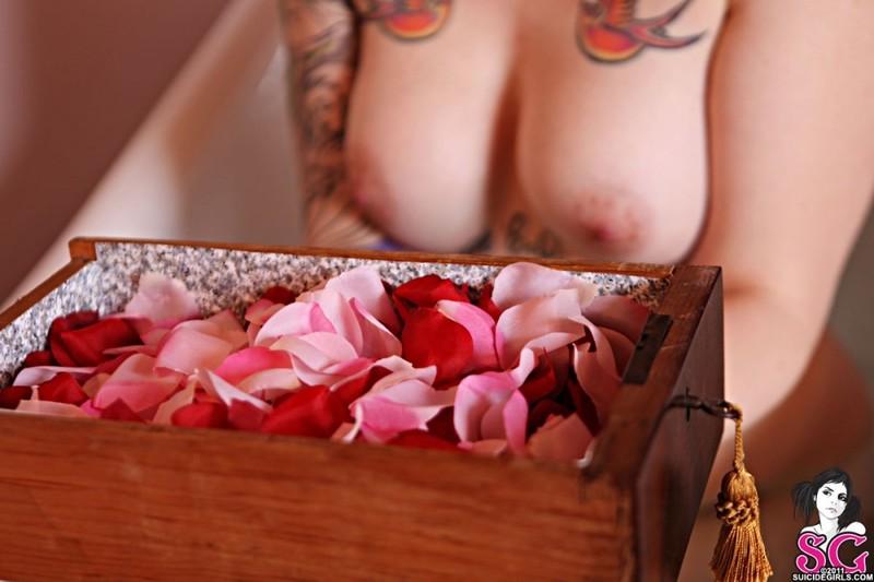 Рыжеволосая кобыла с тату принимает душ с лепестками роз