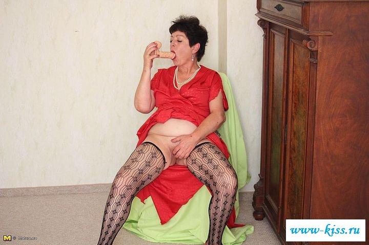Обнаженная бабулька приподняла длинное платье у комода