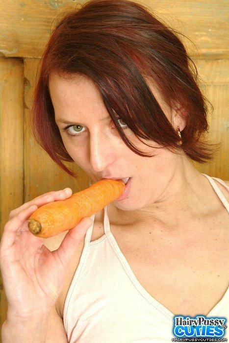 Молоденькая рыжая блядь сует в волосатое влагалище морковку