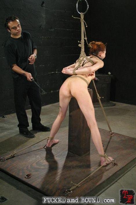 Одетый паренек поставил на колени связанную девку и готовит член для жесткого траха в киску
