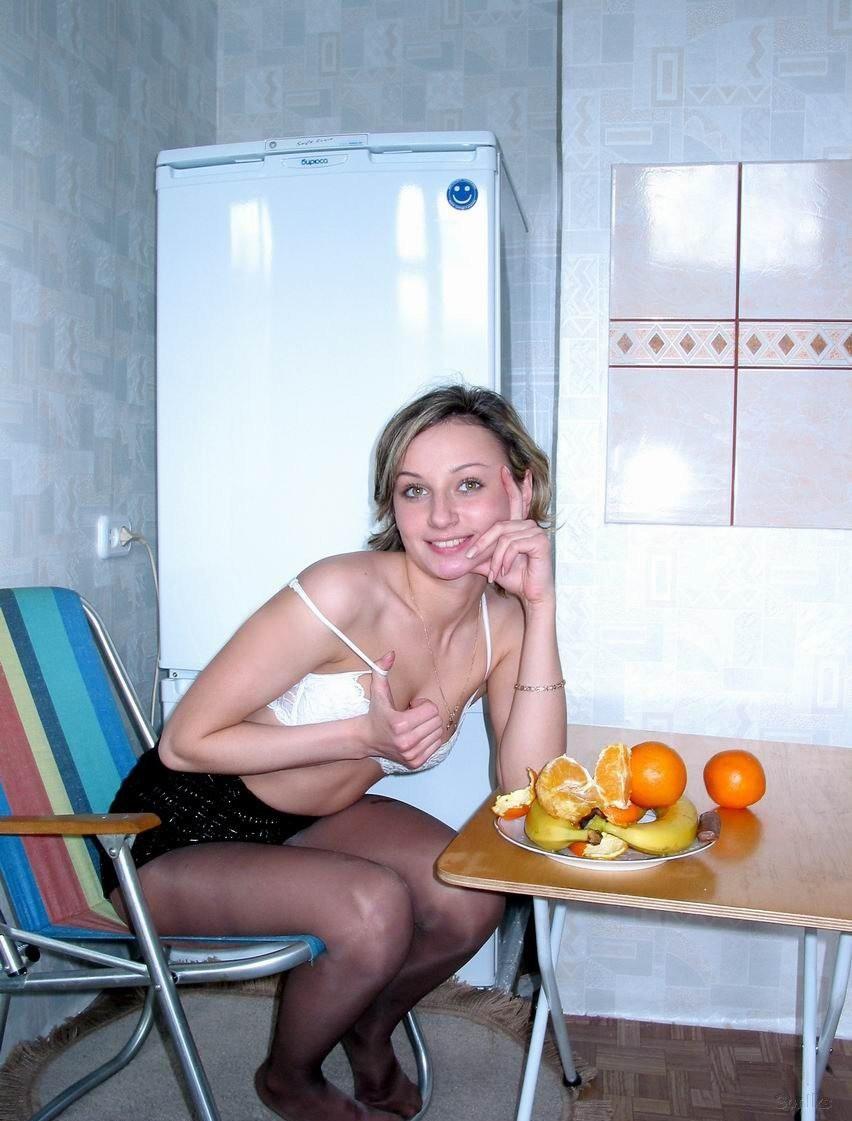 Молоденькая супруга рано утром есть банан на кухне в голом виде